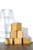 Pile des boîtes en carton sur le fond blanc avec l'ombre d'échelle Image stock