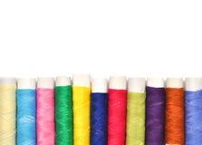 Pile des bobines colorées du fil de lurex d'isolement sur le blanc Photographie stock