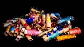 Pile des bobines colorées utilisées de la mise sur pied de fil Photographie stock libre de droits