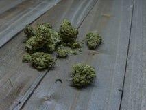 Pile des bourgeons et des brindilles de marijuana sur un Tableau en bois photos stock