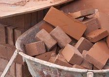 Pile des briques rouges dans une brouette Photographie stock