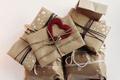 Pile des cadeaux rustiques élégants avec le coeur rouge sur le papier de métier Chri Photographie stock libre de droits