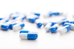 Pile des capsules dispersées sur un fond blanc Photos libres de droits
