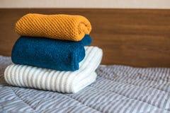 Pile des chandails tricotés confortables sur le lit image stock