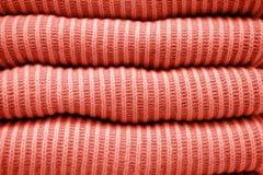 Pile des chandails tricotés de corail vivants chauds dans une rangée image stock
