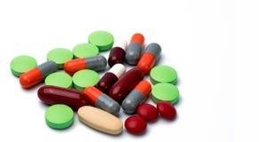 Pile des comprimés colorés et des pilules de capsule d'isolement sur le fond blanc Interaction de drogue, de vitamine, de supplém Images libres de droits
