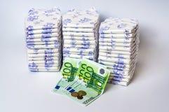 Pile des couches-culottes jetables avec l'euro argent Photos libres de droits