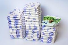 Pile des couches-culottes jetables avec l'euro argent Photographie stock libre de droits