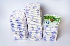 Pile des couches-culottes jetables avec l'euro argent Photos stock