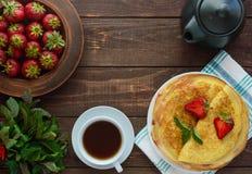 Pile des crêpes d'or avec les fraises et la confiture de fraise, brin décoratif de menthe Photos stock