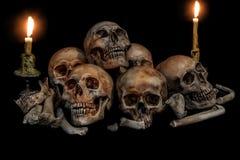 Pile des crânes et des os avec deux bougies Images libres de droits
