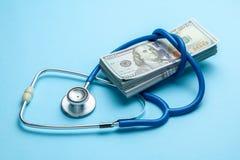 Pile des dollars et du stéthoscope d'argent liquide sur le fond bleu Le concept du strechevka médical ou de la médecine chère, mé image stock