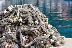Pile des filets de pêche avec des flotteurs sur un quai Images libres de droits