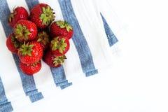Pile des fraises juteuses fraîches sur la serviette dans les rayures bleues, v supérieur Photo stock