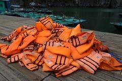 Pile des gilets de sauvetage oranges sur un dock flottant dans la baie long d'ha Photo libre de droits