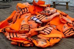 Pile des gilets de sauvetage oranges sur un dock flottant dans la baie long d'ha Image stock