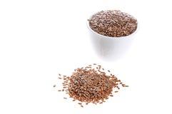 Pile des graines de lin crues d'isolement sur le fond blanc photographie stock
