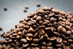 Pile des grains de café rôtis sur un fond noir Photographie stock libre de droits