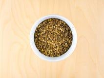 Pile des lentilles brunes sèches crues dans la tasse, centre supérieur Photographie stock