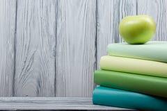 Pile des livres colorés et de la pomme verte sur la table en bois De nouveau à l'école Copiez l'espace Image libre de droits