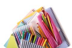 Pile des livres d'école, des crayons, des stylos, de l'équipement et des approvisionnements d'isolement sur le fond blanc Photographie stock libre de droits