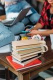 Pile des livres sur la table en bois et jeunes les amis s'asseyant derrière Image stock