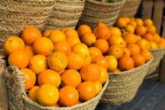 Pile des oranges juteuses dans les paniers en osier sur le compteur du marché photographie stock
