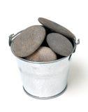 Pile des pebles dans un seau en métal Images stock