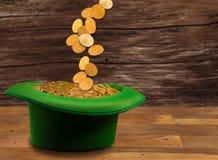 Pile des pièces d'or à l'intérieur de jour vert de St Patricks de chapeau Images stock