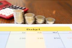 Pile des pièces de monnaie montrant le revenu réduit avec la calculette rouge photographie stock libre de droits