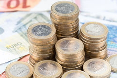 Pile des pièces de monnaie sur des billets de banque Photos libres de droits