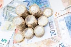 Pile des pièces de monnaie sur des billets de banque Photos stock
