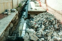 Pile des pierres d'asphalte sur le site de reconstruction de réseau de pipe-lines de chauffage urbain de rue image libre de droits