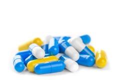 Pile des pilules antibiotiques de couleur sur un fond blanc photos stock