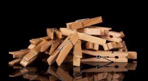 Pile des pinces à linge en bois d'isolement sur le fond noir Image stock
