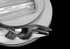 Pile des plats blancs, verres, fourchettes, cuillères. Photos stock