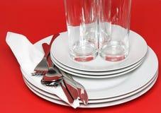 Pile des plats blancs, verres, fourchettes, cuillères. Photo libre de droits