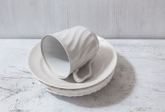 Pile des plats et de la tasse blancs sur la table Photographie stock