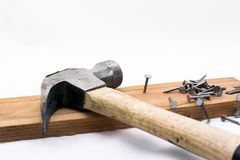 Pile des rivets, des clous et d'un marteau sur le morceau en bois sur le fond blanc Photo stock