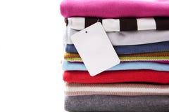 Pile des vêtements avec l'étiquette blanc Photo stock