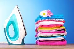 Pile des vêtements colorés et du fer électrique Photos libres de droits