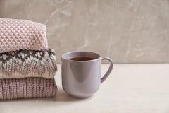 Pile des vêtements et de la tasse tricotés chauds de thé Image libre de droits