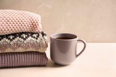 Pile des vêtements et de la tasse tricotés chauds de thé Images libres de droits