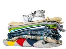 Pile des vêtements et des espadrilles d'isolement sur le blanc Images stock