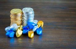 2 pile di monete di Chanukah circondate dai dreidels minuscoli Fotografie Stock