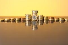Pile di monete con incandescenza dorata Immagini Stock