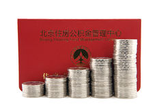 Pile di monete d'argento con il libretto bancario del fondo di accumulazione dell'alloggio Fotografie Stock