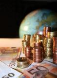 Pile di monete del centesimo e dell'euro davanti ad un globo Fotografie Stock Libere da Diritti