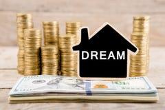 Pile di monete e di banconote in dollari, lavagna sotto forma di una casa con testo & x22; DREAM& x22; Immagini Stock Libere da Diritti