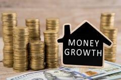 Pile di monete e di banconote in dollari, lavagna sotto forma di una casa con testo & x22; SOLDI GROWTH& x22; fotografia stock libera da diritti